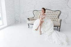 看窗口的新娘,她等待新郎坐大经典沙发 Minimalistic顶楼演播室内部 免版税库存照片