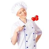 看红色蕃茄的俏丽的妇女厨师垂悬在刀子 图库摄影