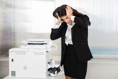 看纸的被激怒的女实业家困住在打印机 免版税库存照片