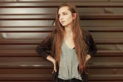 看美丽的女孩倾斜反对金属篱芭 年轻行家女孩在凉快衣裳享用穿戴了 免版税库存图片