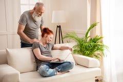 看美丽的成熟妇女的有胡子的人使用在长沙发的膝上型计算机 免版税库存图片