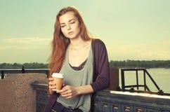 看美丽的棕色毛发的青少年的女孩画象站立和下来 保留外带的饮料的她 都市城市的场面 免版税图库摄影