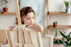 看美丽的肉欲的年轻女人倾斜在画架和  免版税库存图片