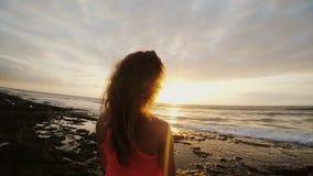 看美好的日落的海滩的少妇 女性观看在天际,风吹的头发 享受海景 股票录像