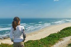 看美好的海景的妇女 免版税图库摄影