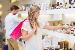 看美容品的一名相当白肤金发的妇女 免版税库存图片