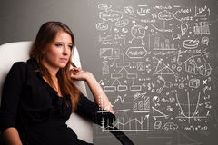 看股市图表和标志的俏丽的妇女 库存照片