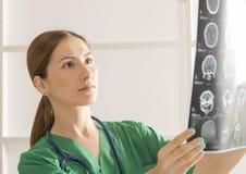 看脑子X线体层照相术的女性医生 库存照片