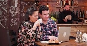 看膝上型计算机和喝咖啡用新月形面包的白种人夫妇 股票录像
