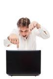 看膝上型计算机和打手势的愉快的年轻人 免版税库存图片