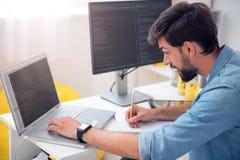 看膝上型计算机和采取笔记的人 免版税图库摄影