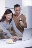看膝上型计算机在厨房里,饮用的酒的微笑的成熟夫妇 图库摄影