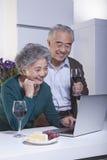 看膝上型计算机在厨房里,饮用的酒的成熟夫妇 免版税库存照片