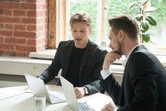 看膝上型计算机屏幕的两个公董事在企业mee期间 图库摄影