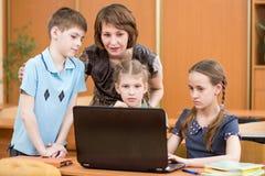 看膝上型计算机屏幕的几个孩子和他们的老师画象在教室 免版税库存图片