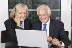 看膝上型计算机白色开会的愉快的资深企业夫妇桌 免版税库存照片