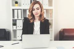 看膝上型计算机的严肃的红发女实业家 免版税库存照片