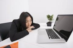 看膝上型计算机的乏味女实业家在办公室 免版税库存图片