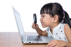 看膝上型计算机的亚裔中国小女孩通过放大器 免版税图库摄影