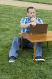 看膝上型计算机的人户外 免版税图库摄影