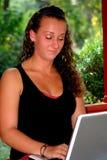 看膝上型计算机的半信半疑的青少年的女孩 免版税库存图片