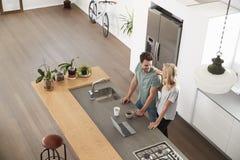 看膝上型计算机的夫妇顶上的看法在现代厨房里 免版税库存图片