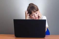看膝上型计算机的女孩 免版税库存照片