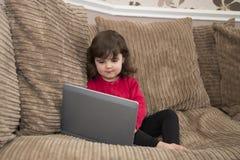 看膝上型计算机的女孩 库存图片