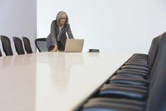 看膝上型计算机的女实业家在证券交易经纪人行情室 免版税库存照片