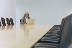 看膝上型计算机的女实业家在证券交易经纪人行情室 免版税库存图片