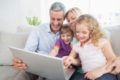 看膝上型计算机的家庭,当坐沙发时 库存图片