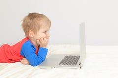看膝上型计算机的小男孩 免版税库存照片