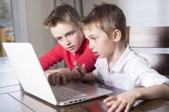 看膝上型计算机的愉快的儿童男孩户内 免版税库存图片