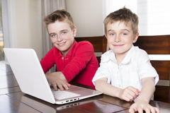 看膝上型计算机的愉快的儿童男孩户内 图库摄影