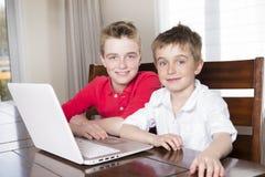 看膝上型计算机的愉快的儿童男孩户内 库存图片