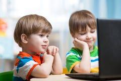 看膝上型计算机的愉快的孩子 图库摄影