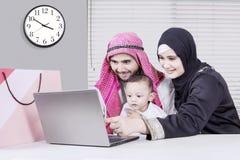 看膝上型计算机的愉快的阿拉伯家庭 免版税库存照片