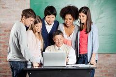 看膝上型计算机的教授和学生  免版税库存照片