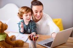 看膝上型计算机的母亲和孩子 图库摄影