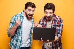 看膝上型计算机的画象两个愉快的年轻人的 免版税库存图片