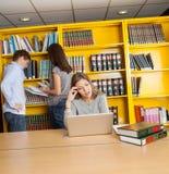 看膝上型计算机的迷茫的学生在大学 免版税库存图片