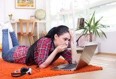 看膝上型计算机的震惊女孩 库存图片