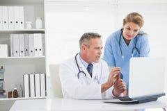 看膝上型计算机的医生和护士 库存图片