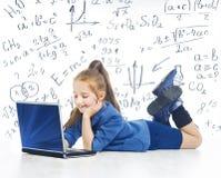 看膝上型计算机,与计算机,小女孩笔记本的孩子的孩子 免版税库存图片