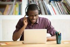 看膝上型计算机scr的耳机的偶然微笑的办公室工作者 免版税图库摄影
