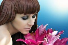 看花和嗅到他们的可爱的夫人画象 免版税图库摄影