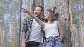 看英俊的年轻人和俏丽的妇女画象站立在野营的杉木森林概念 ?? 股票视频