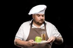 看苹果和杯在板材的汁液的迷茫的厨师画象 免版税图库摄影