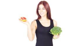 看葡萄柚和拿着的微笑的秀丽妇女硬花甘蓝 妇女坐饮食 素食主义者食物 库存照片