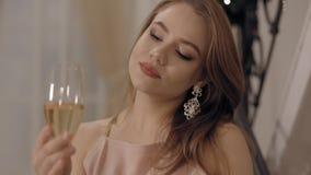 看葡萄酒杯和微笑的桃红色礼服的美丽的年轻女人 股票视频